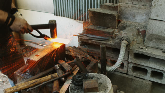 smith beating hot metal on anvil - moulding a shape stock videos & royalty-free footage