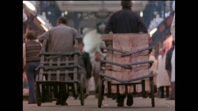 smithfield market porters pulling sack barrows and carrying meat; london, 1978 - moving past stock videos & royalty-free footage