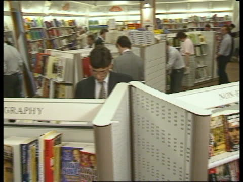 vídeos de stock, filmes e b-roll de h smith's shop as shelves of books seen customers looking at books buying books - livraria