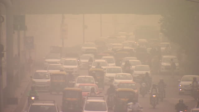 smog covering delhi in india, includes, traffic, children playing football and boy cycling through it - smog stock-videos und b-roll-filmmaterial