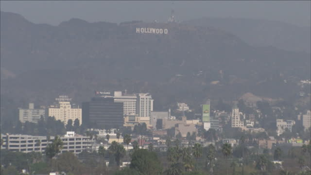 smog hangs over the hollywood sign near the cityscape of los angeles. - smog video stock e b–roll