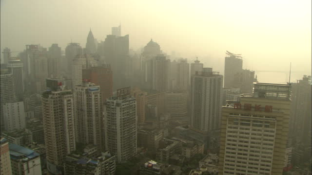 Smog settles over skyscrapers. Available in HD.