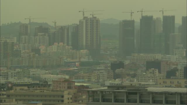 WS HA Smoggy cityscape with cranes on top of skyscrapers, Shenzhen, Guangdong, China