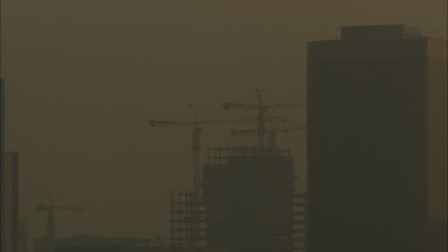 ms smoggy sky with silhouette of crane and skyscrapers under construction, guilin, guangxi zhuang autonomous region, china - guangxi zhuang autonomous region china stock videos & royalty-free footage