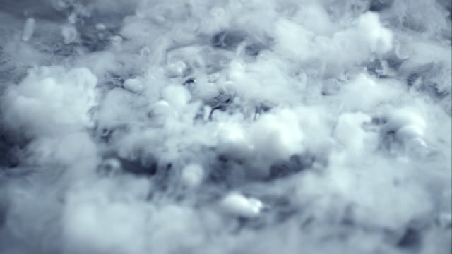 smoke and bubbles form on the surface of dark water.  - chemikalie stock-videos und b-roll-filmmaterial