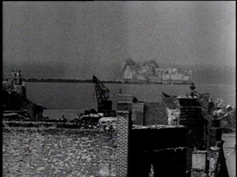 Smoke and destruction along Siegfried Line / tanks firing from shore / smoke over Siegfried Line