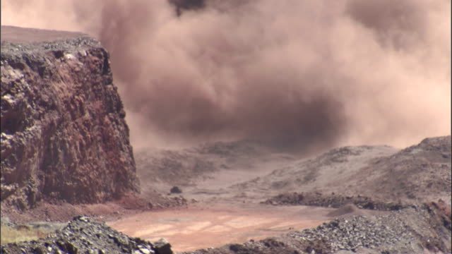 smoke and dust from a mining explosion rise behind a rock cliff. available in hd. - mining stock videos & royalty-free footage