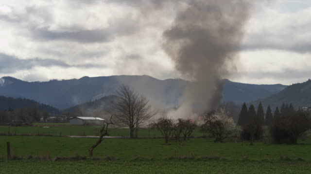 Smoke and flames rising from a burning house across a rural field