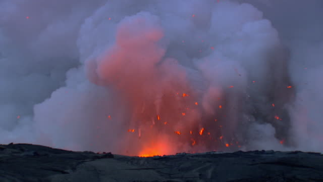 smoke and lava spew from a volcano. - vulkanausbruch stock-videos und b-roll-filmmaterial