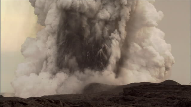 vidéos et rushes de smoke and steam erupt from a volcano. - entrer en éruption