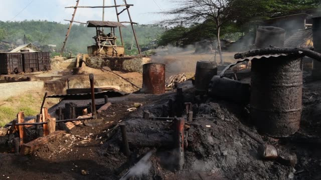 smoke and vapors rise as extracted crude oil is heated in drums during a distillation process in the village of wonocolo east java indonesia on... - destillation stock-videos und b-roll-filmmaterial