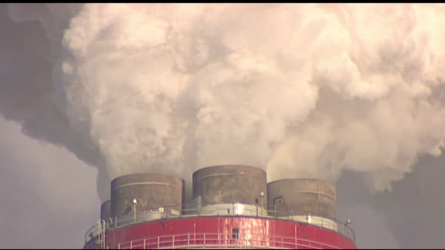 smoke billowing from a power station chimney - smoke physical structure stock videos & royalty-free footage