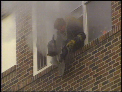 / smoke billowing from burning building / firefighters assisting injured man on street who jumped from building / firefighter hanging out of... - zivilist stock-videos und b-roll-filmmaterial