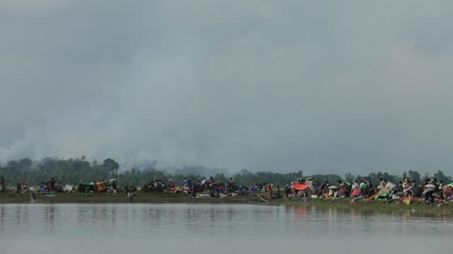 smoke billows above what is believed to be a burning village in myanmar's rakhine state as members of the rohingya muslim minority take shelter in a... - rohingya kultur stock-videos und b-roll-filmmaterial