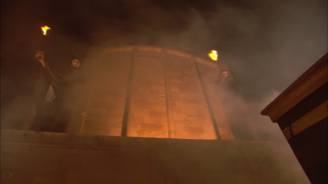 Smoke billows across a temple facade where monks wave flaming torches.