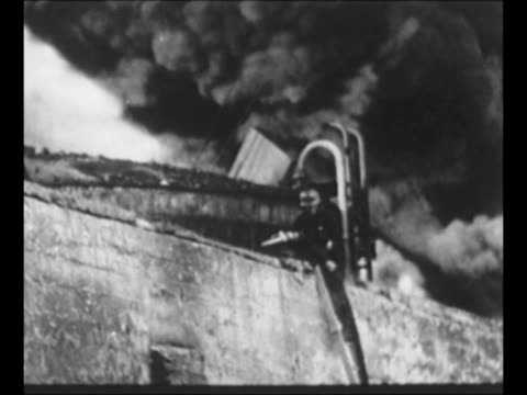 MS smoke billows at Ploiesti oil field in Romania after Allied bombings / MS firefighter on wall sprays hose at burning area as smoke billows behind...