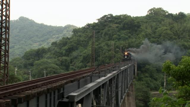 smoke billows from a locomotive crossing a bridge. - 台湾点の映像素材/bロール
