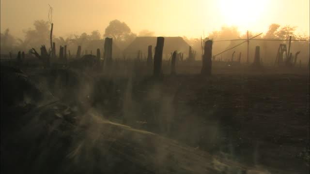 smoke billows from burning logs. - dorf stock-videos und b-roll-filmmaterial
