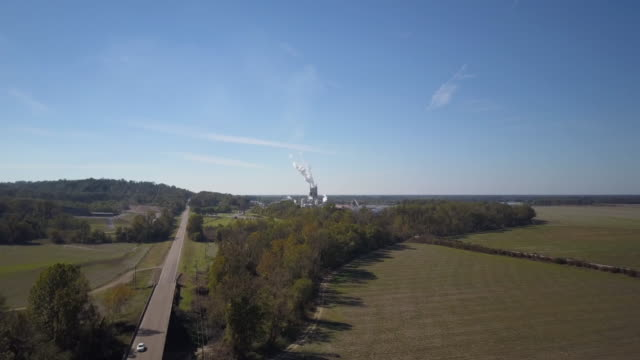 smoke billows from factory near road in rural louisiana, aerial slow push - major road stock videos & royalty-free footage