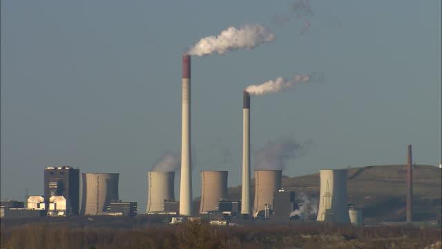 smoke billows from industrial smokestacks. - north rhine westphalia stock videos & royalty-free footage