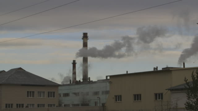 smoke billows from smoke stacks in asbest, wide shot - asbest stock-videos und b-roll-filmmaterial
