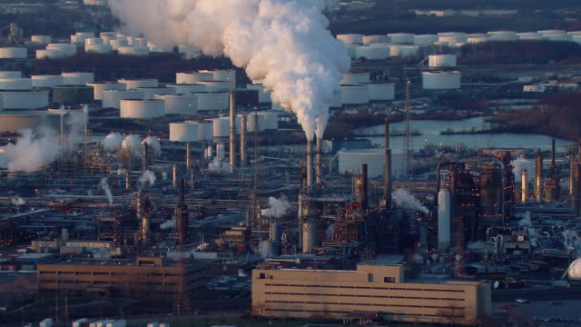 Smoke billows from smokestacks at a New Jersey Oil Refinery.