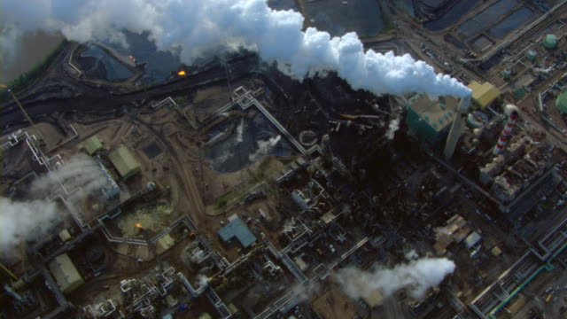 stockvideo's en b-roll-footage met smoke billows from smokestacks at an oil refinery near fort mcmurray, alberta, canada. - luchtvervuiling