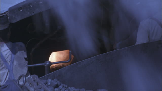Smoke billows out a smokestack on a locomotive.