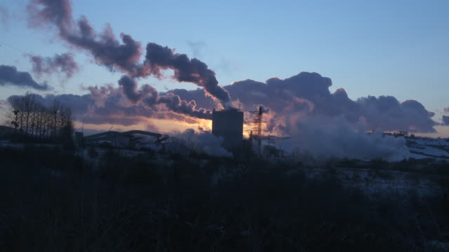 stockvideo's en b-roll-footage met smoke billows out of a factory at golden hour. - vervuiling