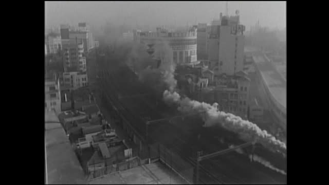 smoke billows out of a steam engine traveling through tokyo, japan. - 古風点の映像素材/bロール