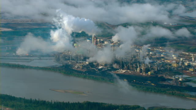 Smoke billows over the Athabasca River and tar sands from an oil refinery in Alberta, Canada.