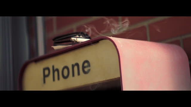 smoke blows from a smoldering cigarette resting on an old-fashioned phone booth in a small town. - anamorphic stock videos & royalty-free footage