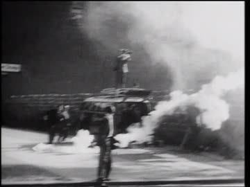 vidéos et rushes de smoke bomb being thrown over berlin wall / man picks it up + throws it back / germany - 1961