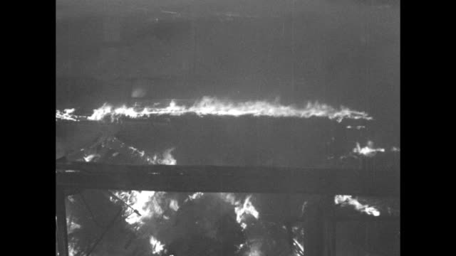vídeos de stock, filmes e b-roll de smoke can see flames / flames and smoke roof structures / fire raging / water spraying across hose spool on top of fire truck in fg firemen on roof... - cilindro veículo terrestre comercial
