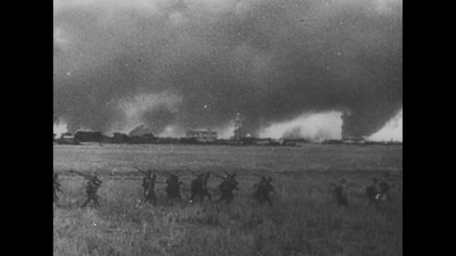 vidéos et rushes de smoke clouds over manila from fires set by invading japanese / line of japanese soldiers crosses grassy field, smoke fills sky above buildings in... - professional occupation