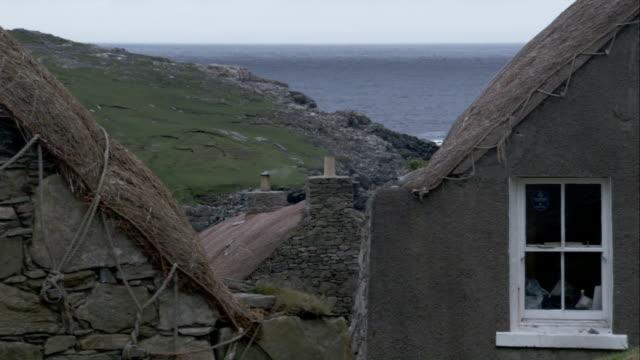 vídeos de stock e filmes b-roll de smoke drifts from a chimney atop a black house in gearrannan scotland. available in hd. - hébridas