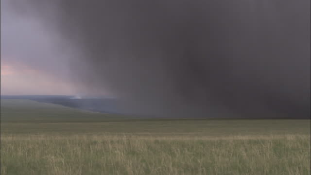 Smoke drifts in from burning fire on steppe, Mongolian steppe