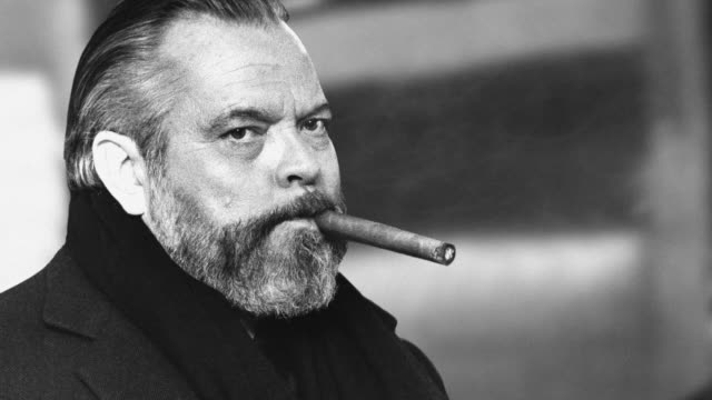 Smoke drifts over a cigar in a portrait photograph of Orson Welles at London's Heathrow Airport.
