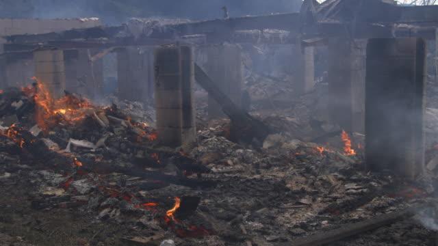 vidéos et rushes de smoke drifts past smoldering rubble of a house destroyed by fire - parpaing