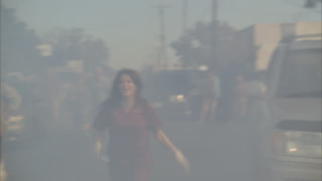 Smoke drifts through the air as panicked civilians flee through a city street.