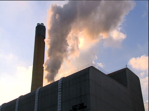 smoke emerges from power plant and drifts into blue sky - carbon monoxide stock videos & royalty-free footage