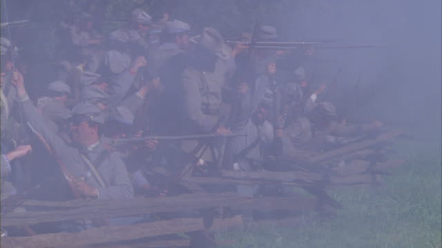 Smoke engulfs Confederate soldiers as they fire rifles across a battlefield.