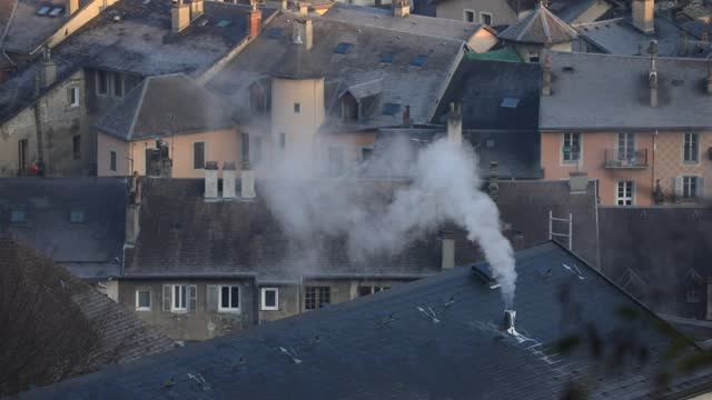 smoke escapes from a chimney on the roof of a building in a cold morning on november 24, 2020 in chambery, france. as the month of december... - cold temperature stock videos & royalty-free footage