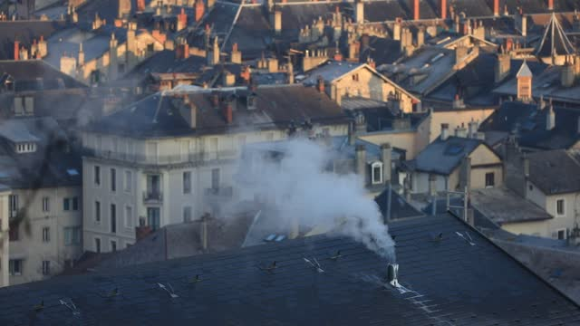 smoke escapes from a chimney on the roof of a building in a cold morning on november 24, 2020 in chambery, france. as the month of december... - heat stock videos & royalty-free footage
