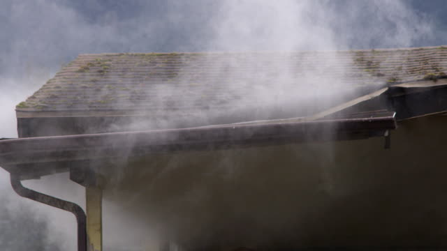 smoke escaping around gutter on the eaves of a burning house - myrtle creek stock videos & royalty-free footage