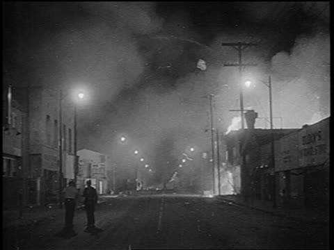 B/W 1965 smoke fire on city street at night after Watts race riots / Los Angeles / newsreel