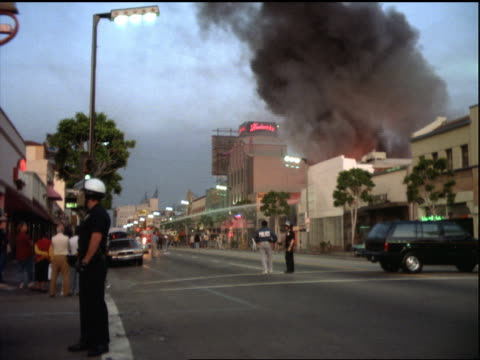vídeos de stock e filmes b-roll de smoke from burning building / policeman on street in foreground / los angeles riots - 1992