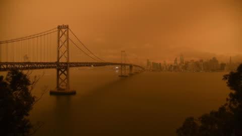 smoke from california wildfires hangs over the bay bridge and the skyline of san francisco, california, usa on wednesday september 9th, 2020. - san francisco kalifornien bildbanksvideor och videomaterial från bakom kulisserna