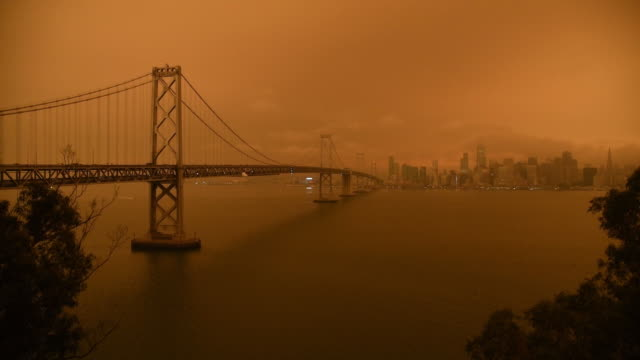 stockvideo's en b-roll-footage met smoke from california wildfires hangs over the bay bridge and the skyline of san francisco, california, usa on wednesday september 9th, 2020. - san francisco california