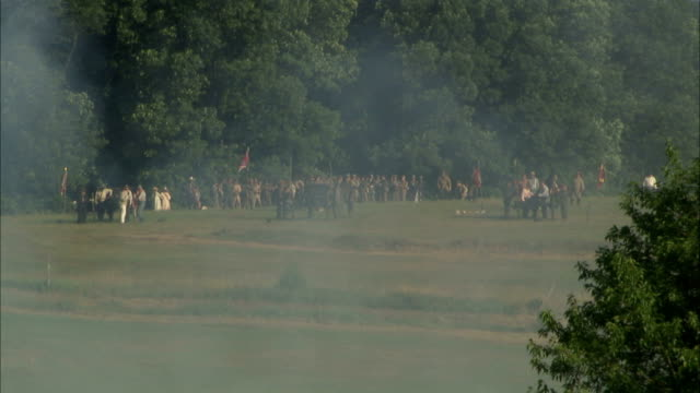 smoke from cannon fire clearing out in fg confederate state army soldiers artillery regiment standing on field w/ cannons in distance pa american... - confederate states army stock-videos und b-roll-filmmaterial